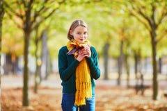 黄色围巾的愉快的少女走在秋天公园的 库存照片