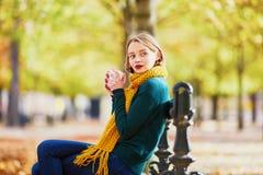 黄色围巾的愉快的少女走在秋天公园的 免版税库存图片