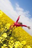 黄色域的愉快的女孩 免版税库存图片