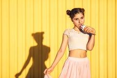 黄色墙壁背景的女孩 免版税库存图片