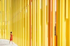 黄色大厦背景的妇女 免版税库存图片