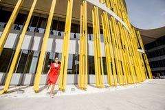 黄色大厦背景的妇女 免版税库存照片