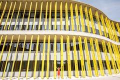 黄色大厦背景的妇女 免版税图库摄影