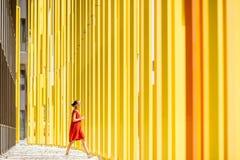 黄色大厦背景的妇女 库存照片