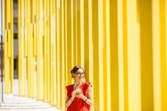 黄色大厦背景的妇女 库存图片