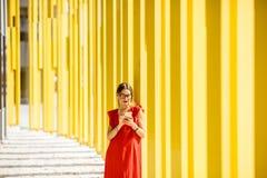 黄色大厦背景的妇女 图库摄影