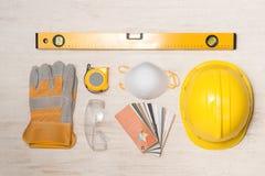 黄色安全帽、被隔绝的手套和锤子 图库摄影