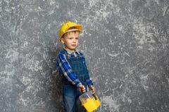 黄色安全帽和一个黄色工具箱的男孩 免版税库存图片