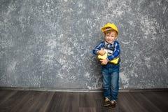 黄色安全帽和一个黄色工具箱的男孩 库存图片