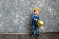 黄色安全帽和一个黄色工具箱的男孩 图库摄影