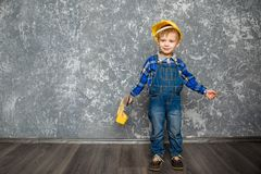 黄色安全帽和一个黄色工具箱的男孩 免版税库存照片