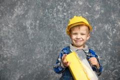 黄色安全帽和一个黄色工具箱的男孩 库存照片