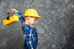 黄色安全帽和一个黄色工具箱的男孩 免版税图库摄影