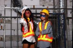 黄色安全帽的美丽的亚裔建筑师工程师妇女 库存图片