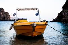 黄色小船航行在河在科孚岛希腊 蓝色清水 美好的横向 船横穿水通过峭壁 旅行 免版税库存照片