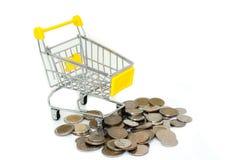 黄色微型购物车或超级市场台车有堆的银色金钱铸造在白色背景隔绝的巴恩 免版税库存照片