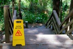 黄色户外小心溜滑湿地板标志在木楼梯附近 免版税库存照片