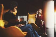 黄色扶手椅子的两个女性同事在办公室 库存照片