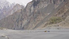 黄色拖拉机开掘的沙子在Hunza河 免版税库存图片
