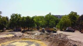 黄色挖掘机开掘基础坑地面和与桶的处理货物对卡车 后勤准备在 股票视频