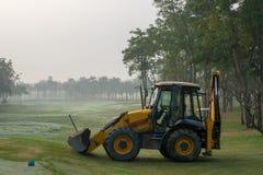 黄色挖掘机& x28; 后面Hoe& x29;运转在高尔夫球法院的汽车 图库摄影