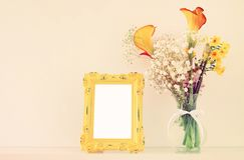 黄色春天美丽的花束的图象在白色桌的空白的葡萄酒照片框架旁边开花 对摄影嘲笑mo 库存图片