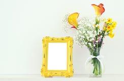黄色春天美丽的花束的图象在白色桌的空白的葡萄酒照片框架旁边开花 对摄影嘲笑mo 免版税库存照片