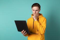 黄色有冠乌鸦工作的确信的年轻帅哥设计师在膝上型计算机,当站立反对蓝色背景时 库存照片