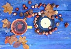 黄色杯子清凉茶和葡萄酒唱片在年迈的木背景与秋天秋叶和栗子 免版税库存图片