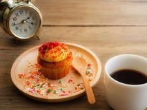 黄色杯形蛋糕投入了一块球状木板材 免版税库存图片