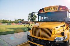 黄色校车正面图在学校前面的-烙记关于 库存照片
