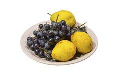 黄色梨和葡萄在板材 库存照片