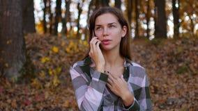 黄色森林妇女的女孩谈话在电话在秋天森林里 股票视频