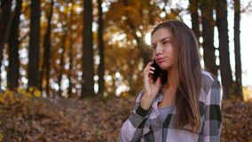 黄色森林妇女的女孩谈话在电话在秋天森林里 影视素材