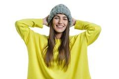 黄色毛线衣和灰色大圈被编织的看在白色的童帽帽子的年轻快乐的美女照相机被隔绝 库存图片