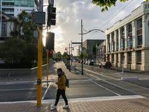 黄色毛线衣的亚裔妇女在边路走在克赖斯特切奇新西兰 免版税库存图片