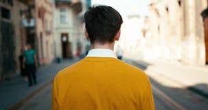 黄色毛线衣的走沿街道,转动围绕和微笑对照相机的年轻少年的背面图 4K 股票录像