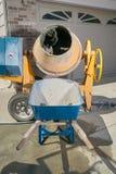 黄色水泥搅拌车机器和独轮车 库存照片