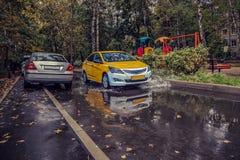 黄色汽车在围场在雨中乘坐在一条湿路 美丽飞溅水从轮子下面 库存图片