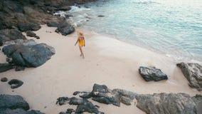 黄色泳装的年轻女人走开在美丽的热带白色沙滩的后面观点的 股票视频