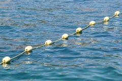 黄色浮体线反对蓝色海的 对开阔水域的制约 强光和波纹在水 图库摄影
