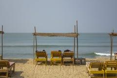 黄色海滩床在一个沙滩的一个竹机盖下反对蓝色海 免版税库存图片