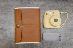 黄色照相机、巧妙的电话和棕色笔记本 概念 图库摄影
