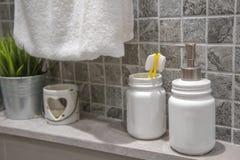 黄色牙刷在白色瓶子在卫生间里, 免版税库存照片