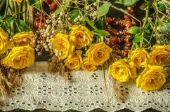 黄色玫瑰、干燥分支和白色鞋带毗邻,用在黑背景的琥珀色的小珠盖 免版税库存照片