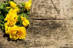 黄色玫瑰在与拷贝空间的土气木背景开花 免版税库存图片