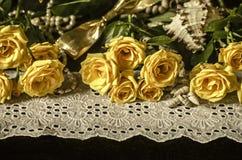 黄色玫瑰,白色麦干燥分支,在白色鞋带边界的芦苇与小珠在黑背景成珠状 库存照片