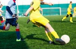 黄色白色运动服戏剧足球的足球队男孩在绿色领域 滴下的技能 成队比赛,训练 免版税库存照片