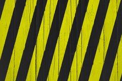 黄色的警报信号和黑条纹被绘在破裂的木头 免版税库存图片