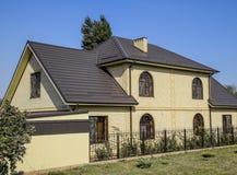 黄色砖和棕色波纹状的屋顶议院由金属制成 在窗口的格子 免版税库存图片